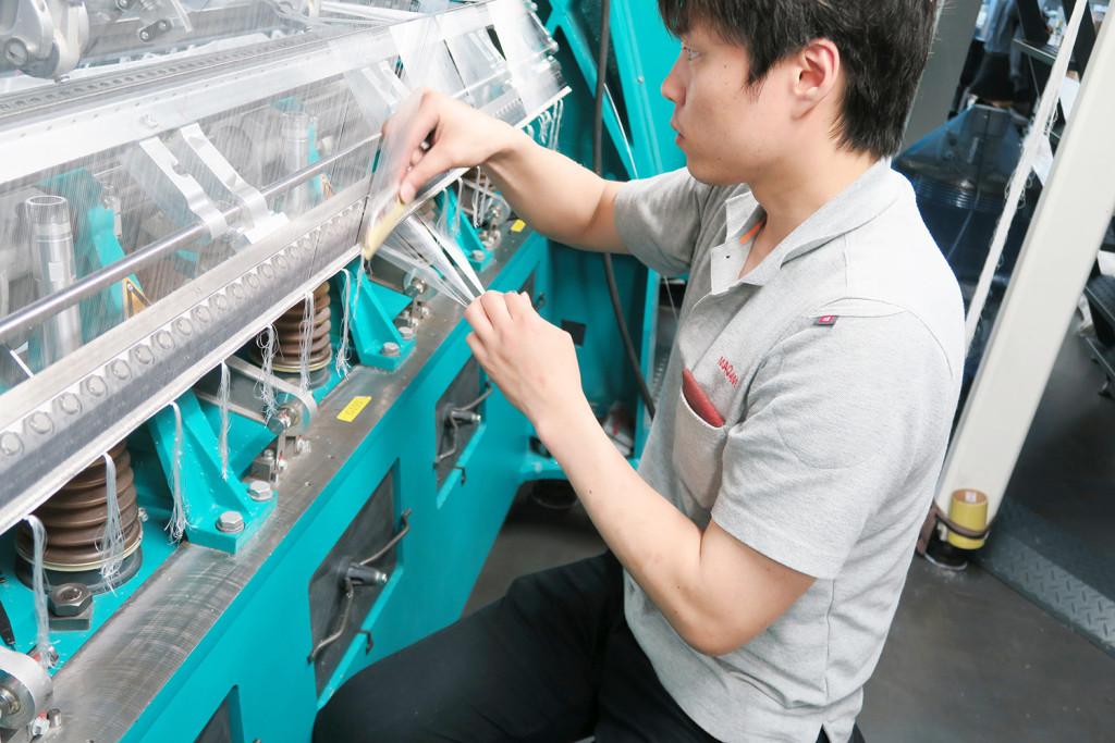 工場では糸をつむぐように編んでいます
